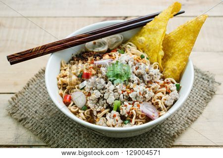 Spicy instant noodle soup with minced pork on wood background.