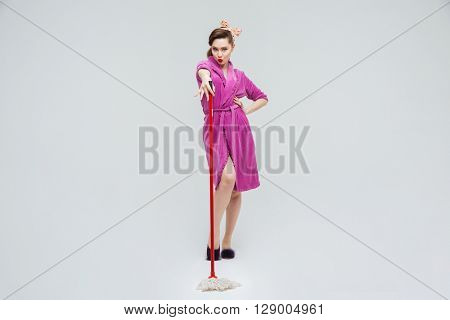 Full length of cute housewife in purple bathrobe posing with mop