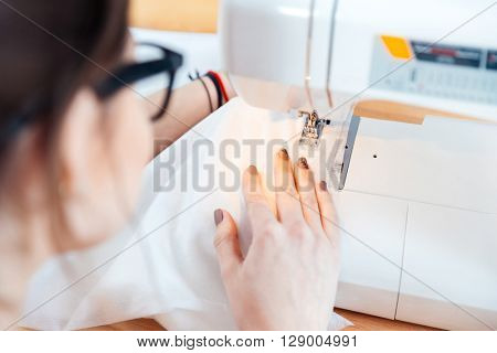 Young woman seamstress in glasses working and sewing in studio