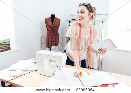 Cheerful charming young woman seamstress with laptop at work