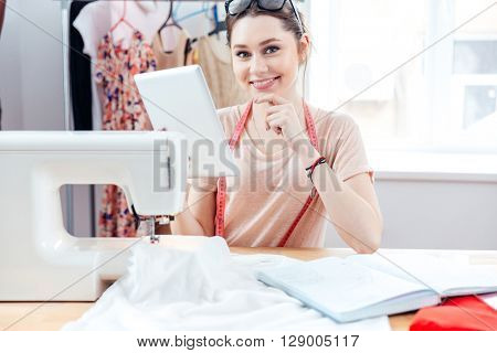 Cheerful beautiful young woman seamstress smiling and using tablet at work