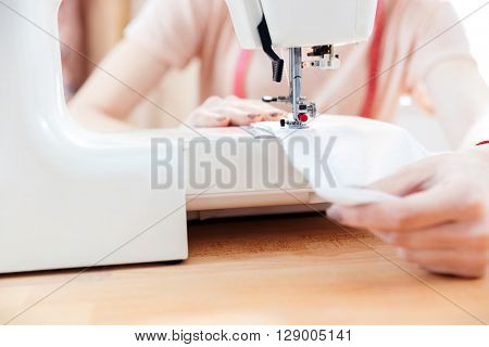 Closeup of young woman seamstress sews clothes and put thread in needle