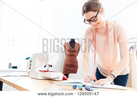 Happy cute young woman seamstress in glasses standing and drawing in workshop