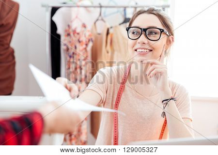 Happy attractive young woman seamstress getting new order at work