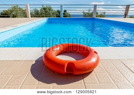 Orange life buoy lying at blue swimming pool in Greece