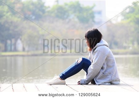 Depressed woman sitting River in the Park