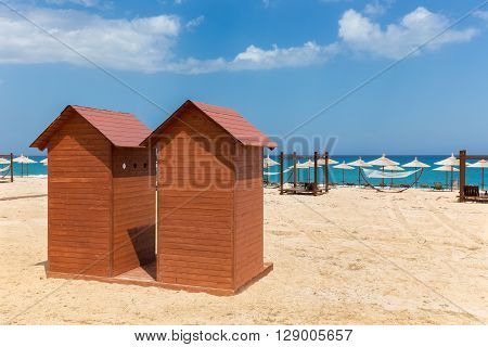 Two wooden beach huts with umbrellas on sandy shore in Greece