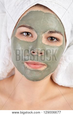 Attractive young woman with applied mud clay mask. Spa beauty procedures skin care treatment concept. White salon towels background