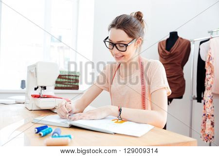Smiling charming young woman seamstress drawing sketches and patterns at the table