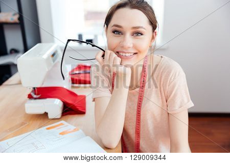 Cheerful attractive young woman seamstress sitting and smiling at work
