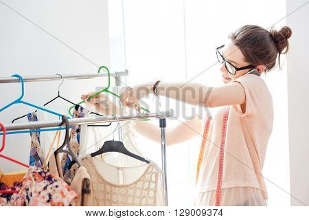 Smiling pretty young woman fashion designer in glasses checking new collection of clothes and talking on cell phone