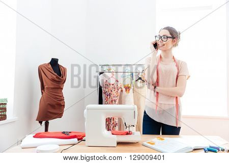 Portrait of cheerful lovely young woman seamstress standing and talking on cell phone in workshop