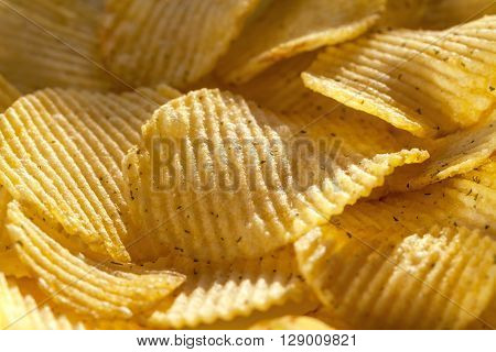 Background of delicious potato chips with spices. Closeup