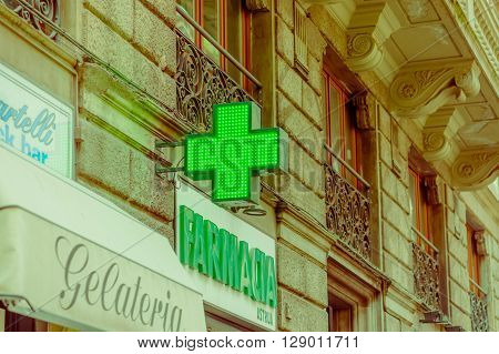 FLORENCE, ITALY - JUNE 12, 2015: Green cross, farmacia sign of medical store. Store sign in historic building, letters on green.