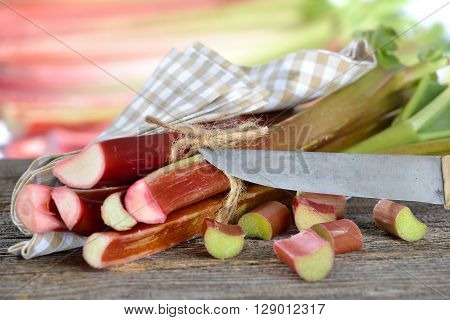 Fresh rhubarb on a wooden table with an old chef's knife, in the background other rhubarb stalks in soft focus
