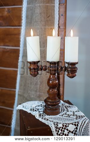 Retro wooden candlestick with candles on wooden table.