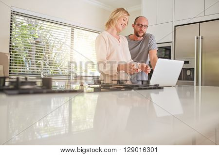 Indoor shot of a happy couple using laptop computer in the kitchen. Woman showing something on laptop to man.