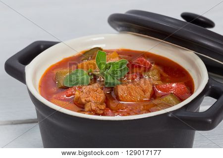 Goulash in a black cocotte with marjoram on white wood.