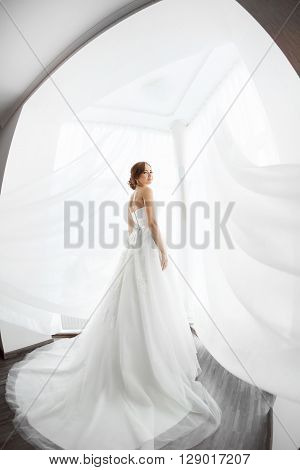 Beautiful young bride in white wedding dress indoors.  Luxuty model standing in full length against big window at home. Girl waiting her groom and looking at camera in bright room. High key, made on fisheye lens photo.