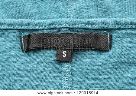 Blank black clothes label closeup on blue cloth