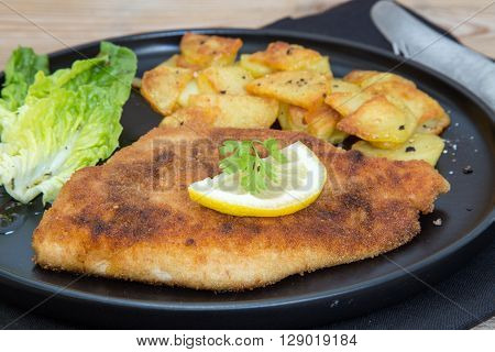 Schnitzel with potatoes salad and lemon top view