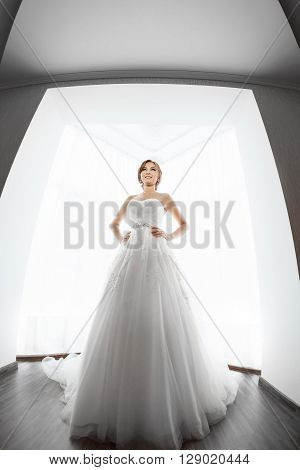 Beautiful young bride in white wedding dress indoors.  Luxuty model standing in full length against big window at home. Girl looking at her groom in bright room. High key, made on fisheye lens photo.