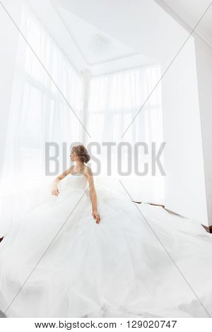 Beautiful young bride in white wedding dress indoors.  Luxuty model sitting against big window at home. Girl waiting her groom in bright room. Beautiful fashion wedding hairdress. High key fisheye photo.