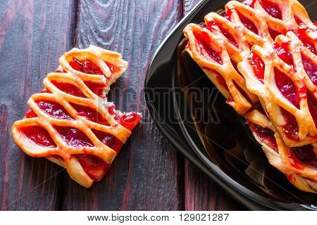 bitten cookie with jam beside a black plate