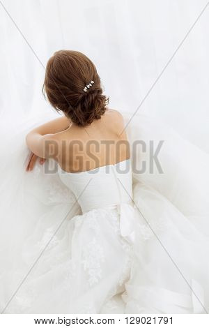 Beautiful young brides back in white wedding dress indoors.  Luxuty model sitting against big window at home. Girl waiting her groom in bright room. Beautiful wedding hairdress. High key photo.