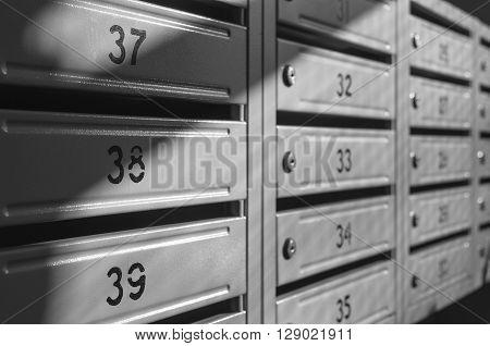grey metallic mailbox array inside apartment houses
