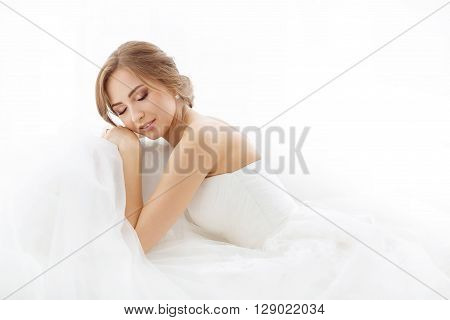 Beautiful young bride in white wedding dress indoors.  Luxuty model lying and sleeping over white backgroung. Girl waiting her groom in bright room. Beautiful fashion wedding hairdress and make-up. High key photo.