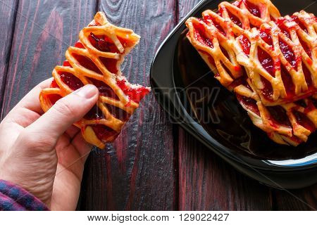 man eating cookies with plum jam on a wooden background