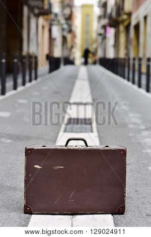 closeup of an old brown suitcase in the middle of a street