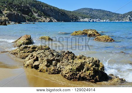 detail of the Aigues Blanques beach in the Mediterranean Sea, in Ibiza Island, Spain, and Cala de Sant Vicent in the background