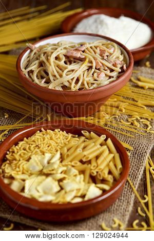 closeup of an earthenware plate with some uncooked pasta, an earthenware bowl with spaghetti alla carbonara, and a bowl with grated cheese on a table