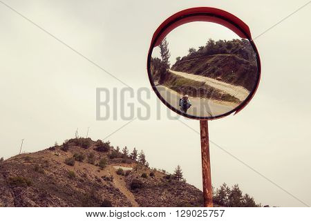 Reflection of a woman hiker with a backpack in the safety mirror on the road. Sunny day on Cyprus. Toned image.