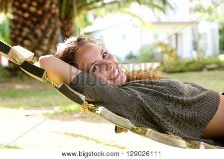 Laughing Woman Lying In Hammock In Front Of Palm Tree