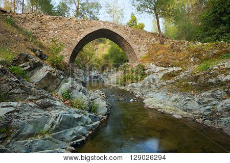 Medieval Venetian bridge on the mountain river in the light of the setting sun.