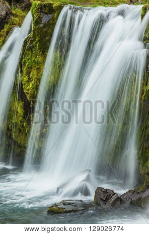 Powerful cascade falls on mossy break. Summer day in cold Iceland