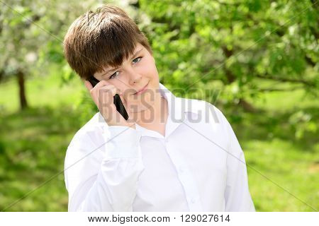 Teen boy talking on the phone outdoors