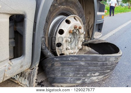 CHIANG RAI THAILAND - SEPTEMBER 27 : closeup damaged 18 wheeler semi truck burst tires by highway street with unidentified driver standing beside on September 25 2015 in Chiang rai Thailand