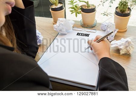 Woman hand writting resume in notebook with pen and paper balls.