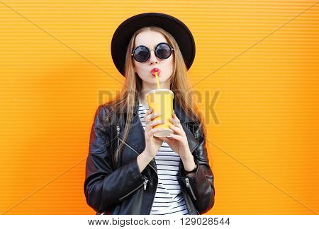 Fashion Pretty Woman In Black Rock Style With Cup Over Orange Background