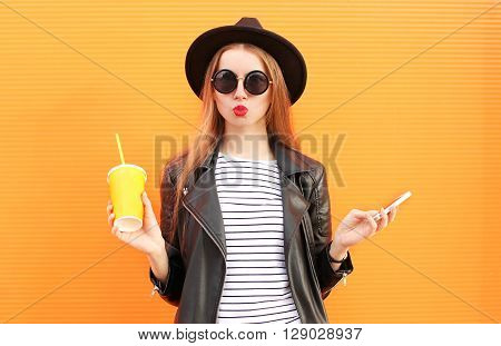 Fashion Pretty Woman With Cup And Smartphone In Rock Black Style Over Colorful Orange Background