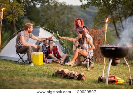 Guys and lassies tapping with bottles and glasses of beer in campground