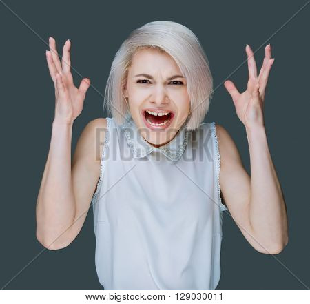 angry young blond woman, isolated against gray studio background