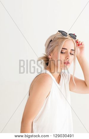 Holidays summer fashion eyes protection and skin care concept. Woman with fashionable black sunglasses, white background. Blonde girl wears sunglasses to protect herself from sun and wrinkles.