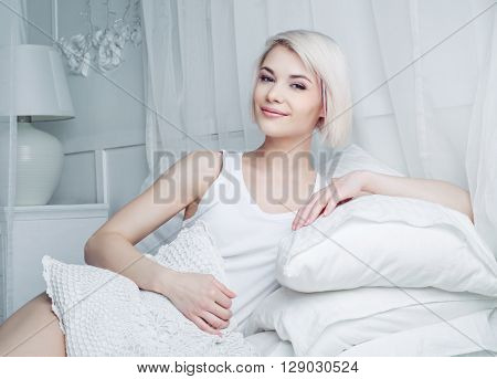 beautiful young blond woman relaxing in bed at home