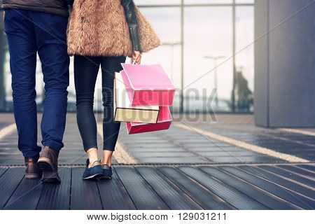 Midsection of couple with shopping bags in city