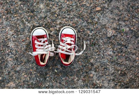 Small baby red shoes converse on grey background